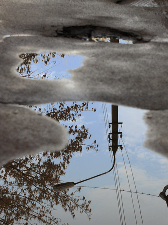 Mirror blurred reflection after a rain of the blue cloudy sky, the silhouette of a street lamp and a tree in a puddle on damaged asphalt.
