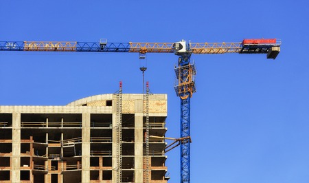 A fragment of the facade of a house under construction, a modern building is being built, an arrow of a tower crane is directed parallel to the roof against a blue cloudless sky.
