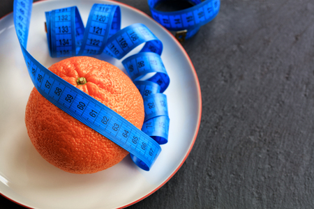 Orange ripe mandarin and meter lie on a white porcelain plate, the concept of a healthy diet for weight loss. Stock Photo