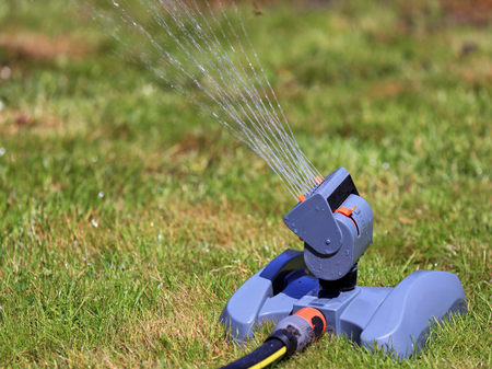 A close-up of a horizontal oscillating sprinkler for lawns that pours a little withered grass