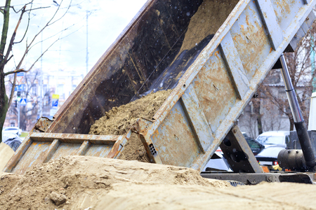 At the construction site of a city street, a cargo truck dumps sand. Stock Photo
