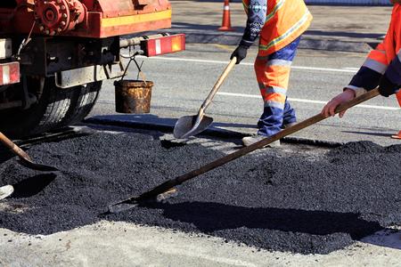 Le groupe de travail des ouvriers routiers renouvelle une partie de la route avec de l'asphalte frais et la nivelle pour la réparation dans la construction de routes.