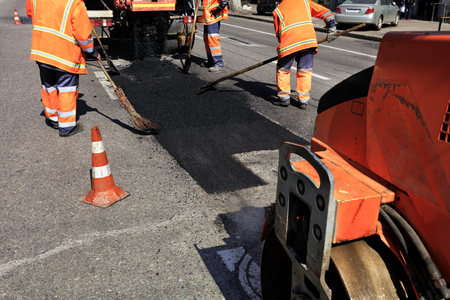 The working team renews a part of the road with fresh asphalt and prepares a section for rolling with a road roller.