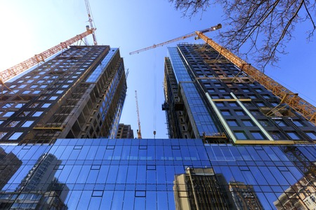 Fragment of the facade of a modern building under construction made of glass and concrete, reflected in the glass walls of adjacent buildings, tower construction cranes pointing upwards. Imagens