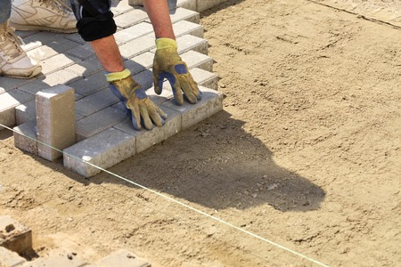 The worker puts the paving slabs along the stretched thread on the prepared flat sandy ground on the sidewalk.