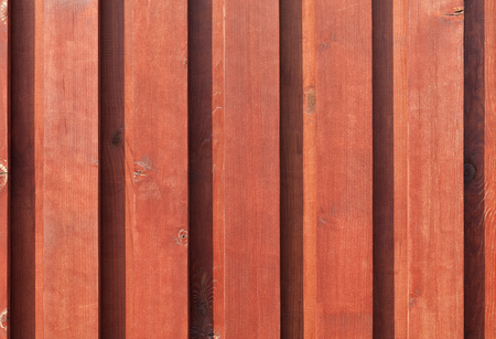 The texture of the new brown-red wooden fence close-up in the rays of sunlight.