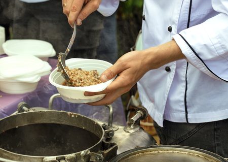 The concept of caring for the poor and the elderly: social workers feed people buckwheat porridge on the street. Stock Photo