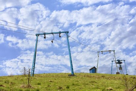 The frame of the mountain cable lift stands apart on the top of the mountain against the background of a deep blue sky with white clouds in the Carpathians.