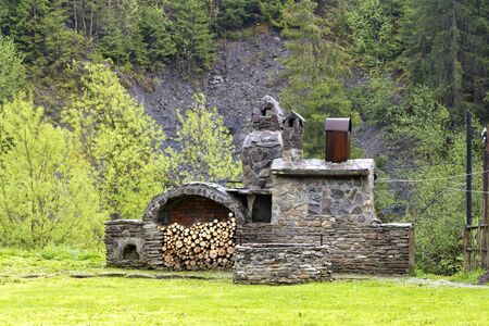 Old stone oven with wood, spit for meat and a smokehouse for cooking on the street in the Carpathians.