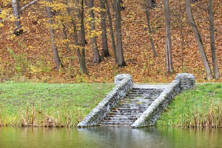 On the shore of the autumn forest pond, the old, moss-covered, stone steps touch the calm surface of the water. Stock fotó