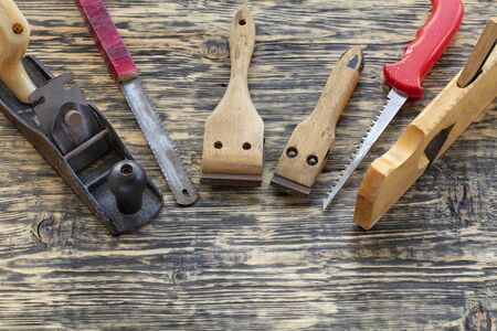 Old carpentry tools, planers, handsaws and cycles lie on a wooden table.