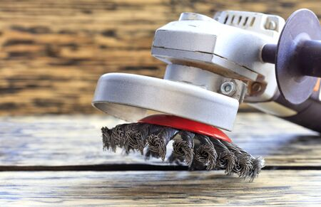 Angle grinder with abrasive wire brushes lies on the background of a wooden table.