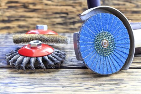 Angle grinder with grinding disc brushes and abrasive wire brushes lies on the background of a wooden table.