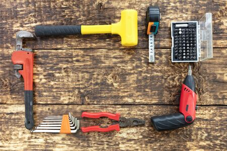 Old hand tools, pliers, hammer, tape measure, adjustable wrench, electric screwdriver with a set of bits, a set of hex keys are located on the old wooden table and create a frame. Фото со стока