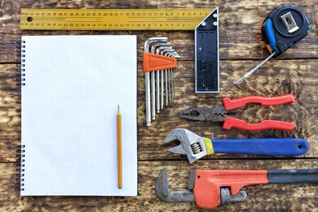 Old hand tools, pliers, tape measure, adjustable wrenches, a set of hex keys indicate an empty notebook with a pencil against the background of an old wooden table. Фото со стока