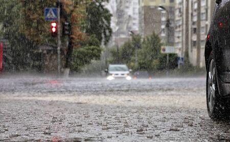 Lluvia torrencial en la encrucijada y luz roja reflejada en el flujo de agua en una calle de la ciudad.