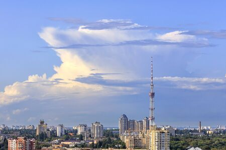Cityscape of summer at noon with a television tower against the magical clouds of blue sky.