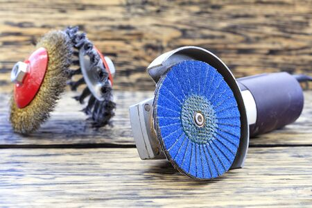 Angle grinder with grinding disc brushes and abrasive wire brushes lies on the background of a wooden table in a blur..