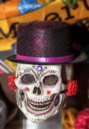 Halloween, skull doll with a smile, decorated with female makeup in a black and red hat, isolated on a worn background.