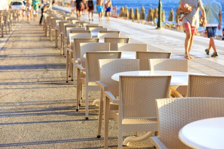 Tables and chairs of the beach cafe are located along the promenade where vacationers walk.