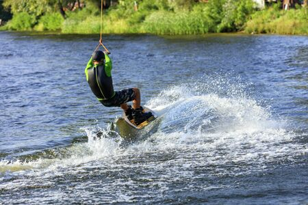 A wakeboarder rushes through the water along the riverbank, holding the cable with both hands and leaving a waterway behind him.