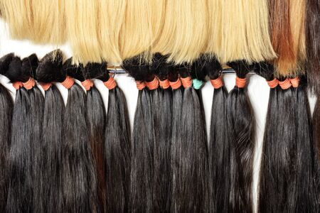 Haircare female hair, technology, style and beauty concept. Natural black and white, brown, shiny, colored shiny healthy human hair bundles for extension and weave wigs making. 스톡 콘텐츠