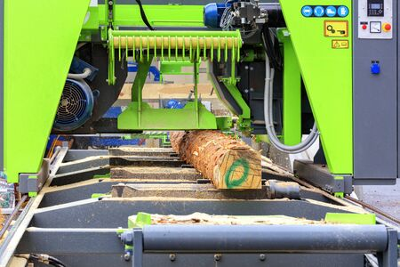 Woodworking, lumber, pine boards are made from large logs in a modern automatic sawmill.