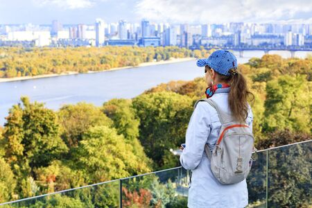A traveler enjoys a view of the Dnipro River and the left bank of Kyiv from a high hill on an autumn bright warm day.