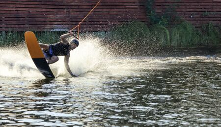 A wakeboarder rushes through the water along the riverbank, holding the cable with one hand and raising a spray of water behind him on a steep turn. Banco de Imagens
