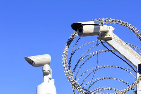 Territory perimeter security. Barbed wire fence and cameras protect against intruders. Stockfoto