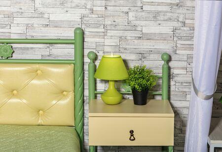 El tono verde pastel y amarillo fresco de la cama, una maceta verde, una lámpara de mesa elegante en una mesita de noche amarilla se combinan perfectamente en una esfera de pared gris de viejos tablones de madera. Foto de archivo