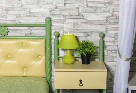 Fresh pastel green and yellow tone of the bed, a green flowerpot, an elegant table lamp on a yellow bedside table perfectly combines on a gray wall sphere of old wooden planks. Stock Photo