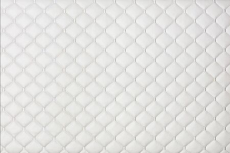 White leather furniture background and texture stitched with silver diamond-shaped threads.