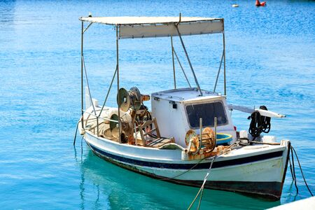 A small old wooden fishing boat with betallic reels for reeling up fishing nets, which sways in motion on the waves at the pier.