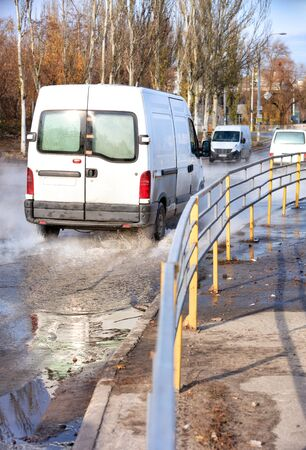 An accident on a heating main, a rupture in a pipe with hot water, trucks driving along a flooded road, water vapor forms a smokescreen over the asphalt, and a metal fence separates the carriageway from the sidewalk.
