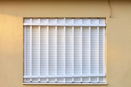 White metal shutters on the window of the yellow facade of the house are additionally closed by a white metal grille in the soft rays of the setting sunlight, image with copy space.