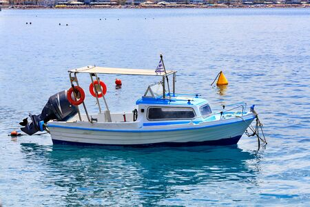 A small rescue boat with a powerful motor and orange lifebuoys on board sways on the sea waves of the Greek coast against the background of the beach coastline, image with copy space.