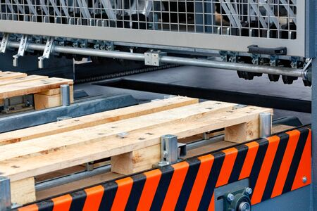 Production of wooden pallets on a modern automatic line, a fragment of the connection of wooden planks.