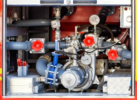 A powerful water pump and foaming unit with pressure sensors, valves and taps are located in the middle of the cargo compartment of the equipped fire truck. Archivio Fotografico