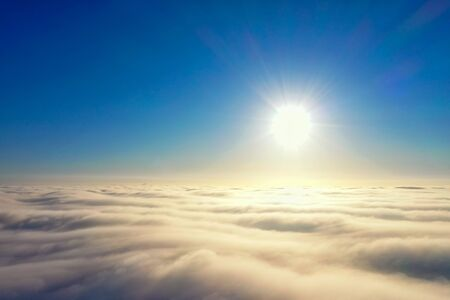 Aerial photos, bright sun over a cover of gray clouds in blure, photo about 500 meters of height made with drone of last generation from a height of a drone.