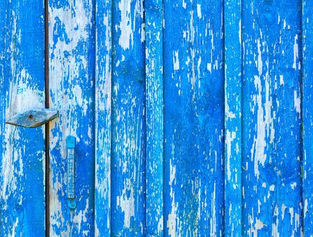 The old wooden texture is painted with blue weathered and peeling paint.