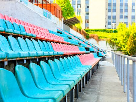 The rhythmic rows of empty turquoise and red plastic chairs of an old sports stadium against the background of sunlight in the background.