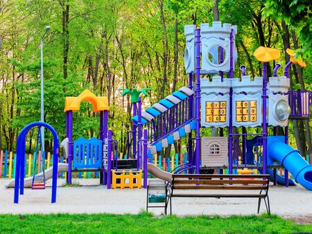 A beautiful children's multi-colored playground with various attractions and sports equipment in the city summer park.