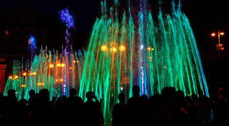 Sagome scure di persone intorno alla fontana a tarda sera, luci al neon multicolori illuminano i getti di una potente fontana canora urbana.