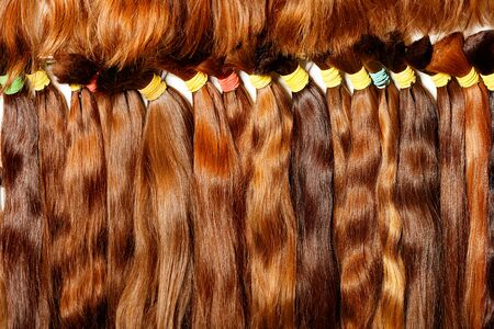 Natural brown with a different shade, shiny, colored shiny healthy human hair bundles for extension and weave wigs making. Haircare female hair, technology, style and beauty concept.