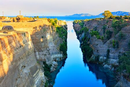 The Corinth Canal in the morning summer day illuminates the bright rising sun of Greece, a view of the Gulf of Corinth from the height, the channel connects the Saronicos of the Aegean Sea and the Corinthian Gulf of the Ionian Sea.