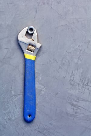 In an old adjustable wrench with a rubberized blue handle, an old metal nut is clamped, an image against a gray concrete background, with copy space.