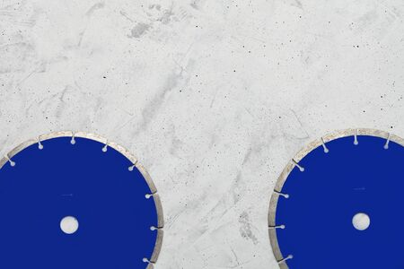 Blue cutting blades with diamond for cutting concrete and reinforced concrete using an angle grinder on a gray concrete background, image with copy space.