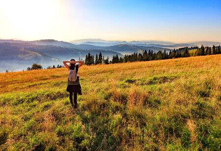 A young woman breathes the aroma of wild herbs and flowers early in the morning in the rays of the rising sun, meets dawn on a hill meadow and looks at the foggy Carpathian mountains.