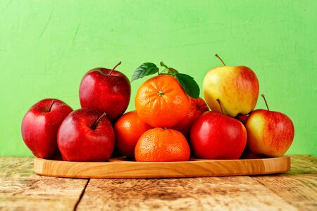 Red ripe apples and mandarins with green leaves lie on a wooden tray on an old wooden table on light green background, image with copy space.